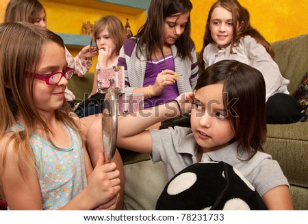 Group of six little girls put on makeup and style their hair - stock photo