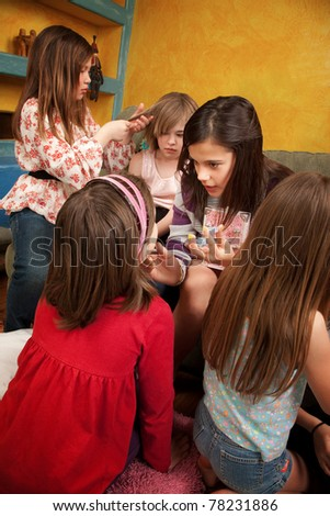 Group of six little girls styling hair and painting face - stock photo