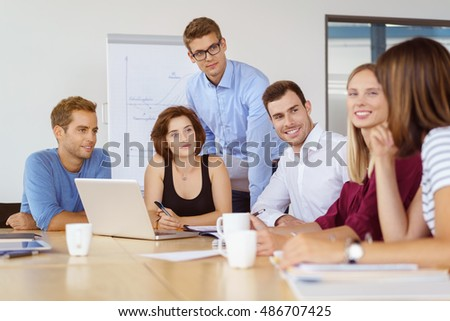 Group of six male and female coworkers listening to each other during meeting in office
