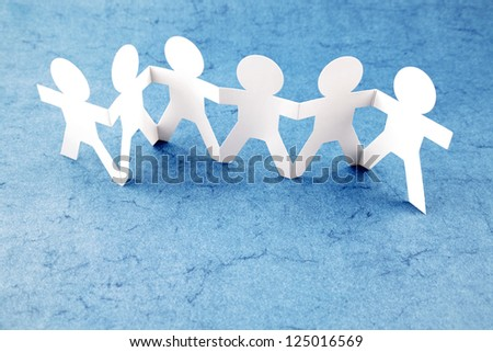 Group of six paper chain people holding hands together - stock photo