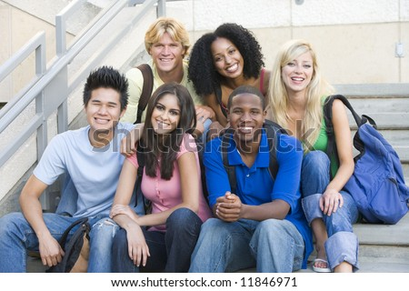 Group of six students outside sitting on steps - stock photo