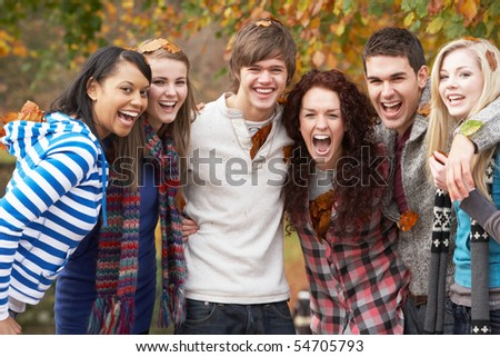 Group Of Six Teenage Friends Having Fun In Autumn Park - stock photo
