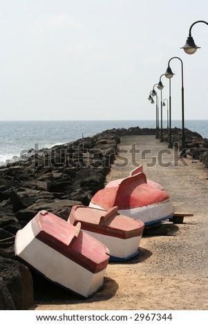 group of 4 small rowing boats pulled up on a breakwater for the winter - stock photo