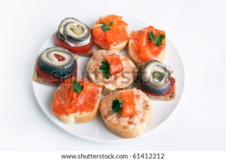 group of small sandwiches ( canape )  with  herring and smoked salmon on a white plate - stock photo