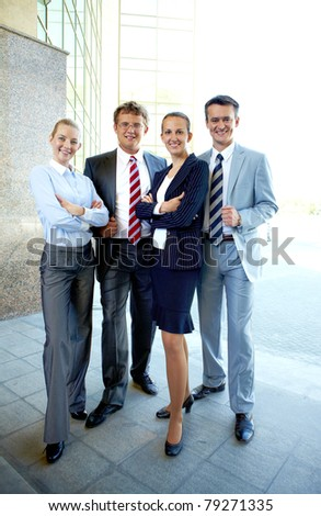 Group of smart business partners looking at camera outside - stock photo