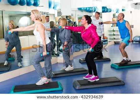 Group of  smiling adult men and women training in  gym with dumbbells. Selective focus  - stock photo