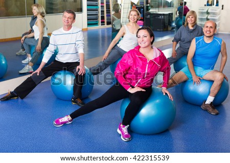 Group of smiling adults doing aerobics with balls in a sport club - stock photo