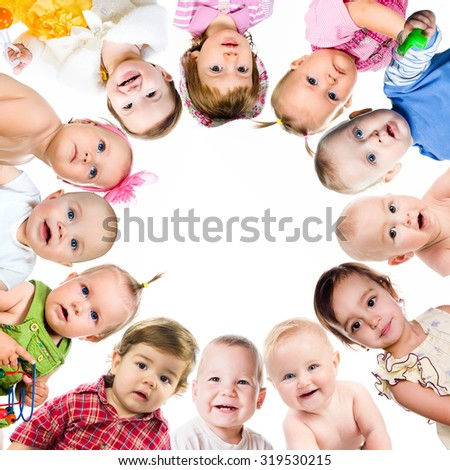 Group of smiling babies standing in huddle on white - stock photo