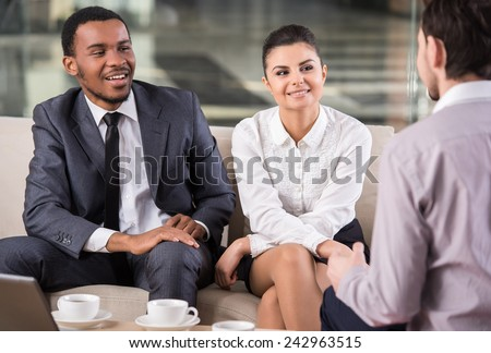Group of smiling business partners are interacting in office during coffee break. - stock photo