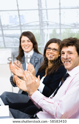 Group of smiling businesspeople sitting in row on training and clapping. - stock photo