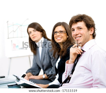 Group of smiling businesspeople sitting in row on training and looking at trainer positively. - stock photo