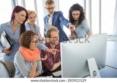 Group of smiling businesspeople using computer together in office - stock photo