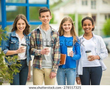 Group of smiling cheerful teenagers drinking a coffee at the park after lessons. - stock photo