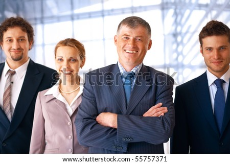 Group of smiling confident business people with their leader at the office.