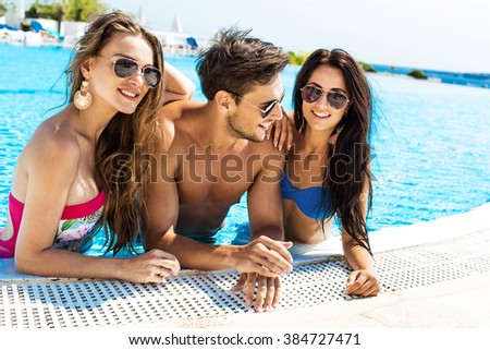 Group Of Smiling Friends Having Fun In Swimming Pool And Wearing Sunglasses - stock photo