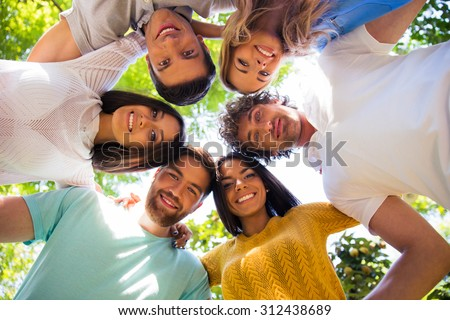 Group of smiling friends hugging together at the park in a circle - stock photo