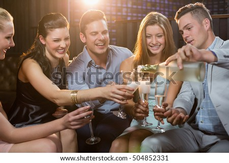 Group of smiling friends interacting while having a glass of champagne at bar