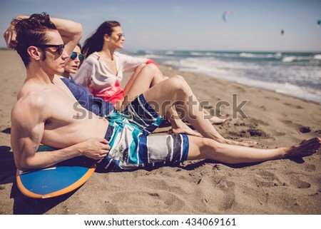 Group of smiling friends wearing swimwear and sunglasses with surfboards on beach. Summer concept - stock photo