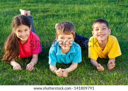 Group of smiling kids lying on the green grass meadow - stock photo