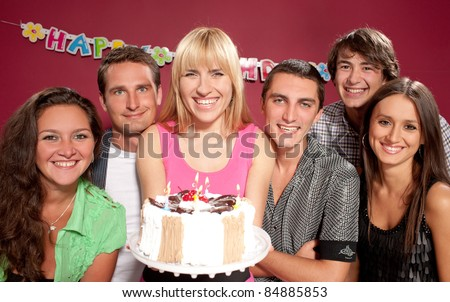 Group of smiling people with pie at birthday party