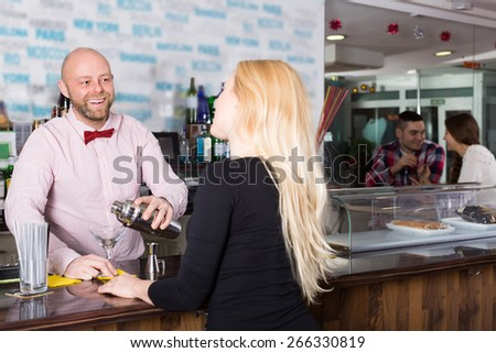Group of smiling positive young adults hanging out in bar