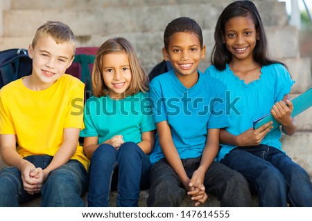 group of smiling primary school students outdoors - stock photo