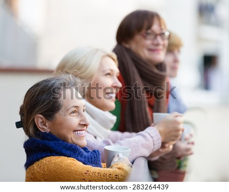 Group of smiling senior female friends drinking tea at balcony - stock photo