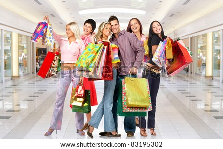 Group of smiling shopping people in modern mall. - stock photo