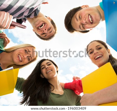 Group of smiling students staying together and looking at camera on sky background - stock photo