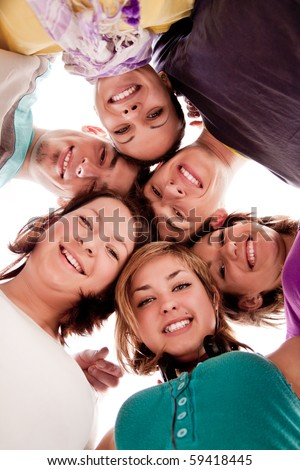 group of smiling teenagers in circle �¢���� view from below