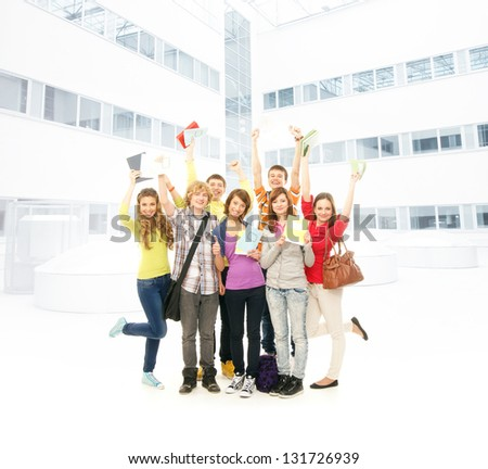 Group of smiling teenagers staying together and looking at camera near the school building - stock photo