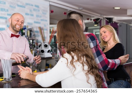 Group of smiling young friends hanging out in bar - stock photo