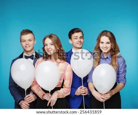 Group of smiling young people holding white balloons on blue background. Hipster style.  - stock photo