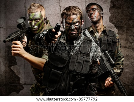 group of soldiers aiming with rifles against a grunge bricks wall - stock photo