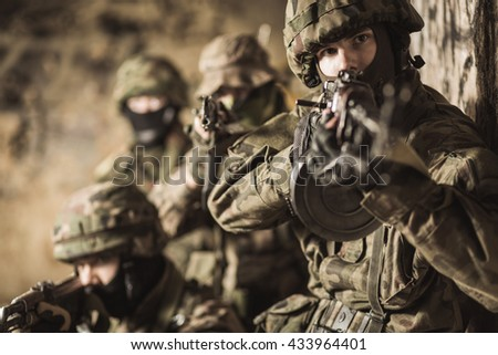 Group of soldiers holding guns, aiming from cover