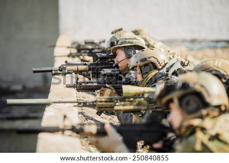 group of soldiers lie and aim at - stock photo
