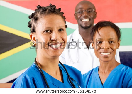 group of south african medical workers portrait in front of south african flag - stock photo