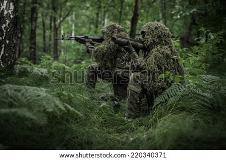 Group of special forces soldiers in forest, aiming with rocket launcher. Soldiers dressed in ghillie camouflage on nature. - stock photo