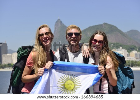Group of sport fans friends traveling at Rio de Janeiro holding Argentinian flag, with Christ Redeemer in the background. - stock photo