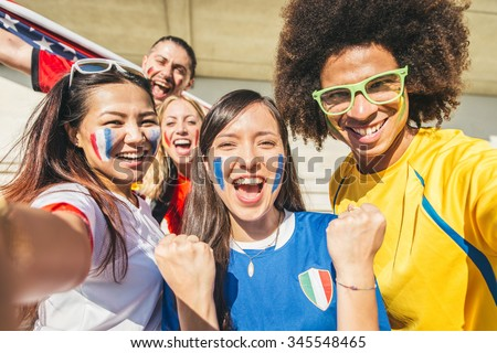 Group of sport supporters at stadium taking selfie - Fans of diverse nations screaming to support their teams - Multi-ethnic people having fun and celebrating on tribune at a sport event  - stock photo