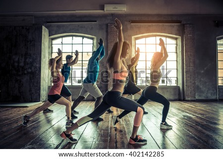 Group of sportive people in a gym training - Multiracial group of athletes stretching before starting a workout session - stock photo
