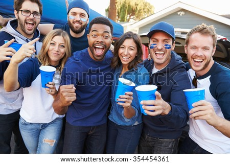 Group Of Sports Fans Tailgating In Stadium Car Park - stock photo