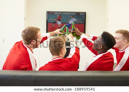 Group Of Sports Fans Watching Game On TV At Home - stock photo