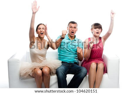 Group of sports fans watching the competition sitting on a white sofa
