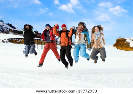 Group of sports teenagers different ethnicity jumping in mountains, over blue sky