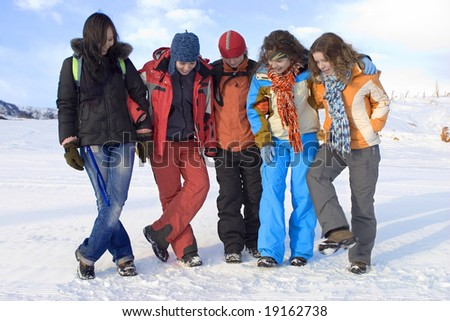 Group of sports teenagers in mountains, over blue sky - stock photo