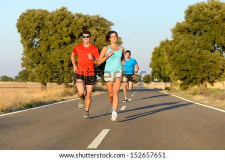 Group of sporty people running in country road competition. Cheerful athletes on marathon run challenge. - stock photo