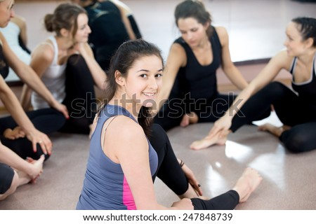 Group of sporty young female friends chatting, resting, on break after exercises in sports club, gym class. Focus on smiling teenage female athlete in color sportswear - stock photo