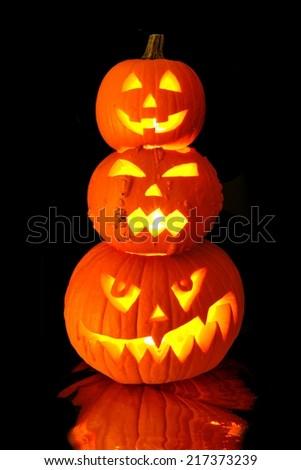 Group of stacked Halloween Jack o Lanterns with black background - stock photo