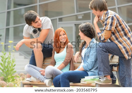Group of student friends sitting bench outside college hanging out - stock photo